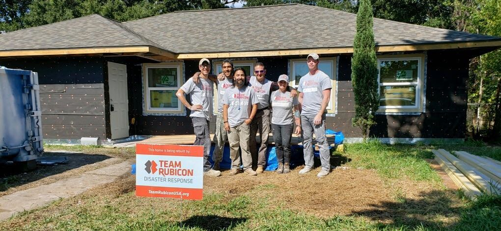 Team Rubicon team members in front of a new home.